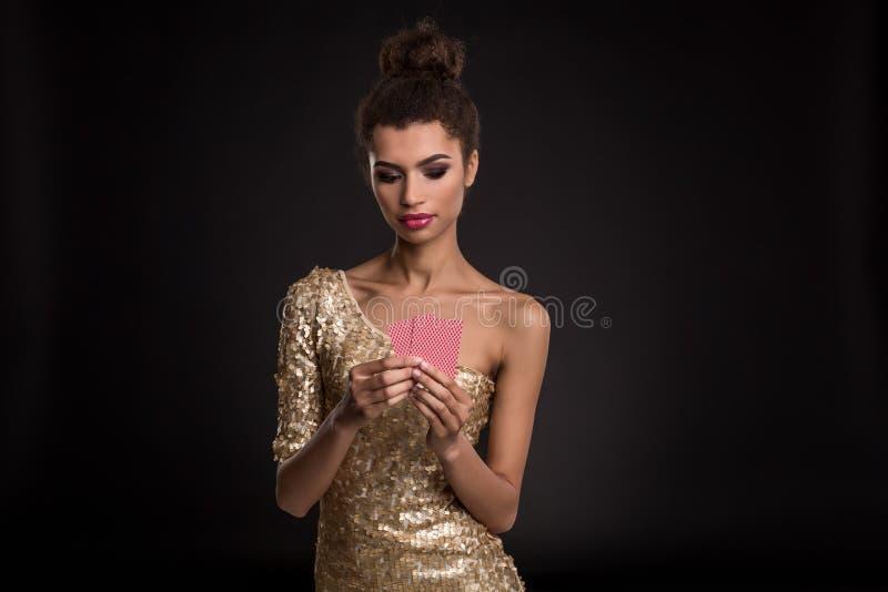 Νίκη γυναικών - νέα γυναίκα σε ένα αριστοκρατικό χρυσό φόρεμα που κρατά δύο κάρτες, ένα πόκερ του συνδυασμού καρτών άσσων συγκινή στοκ εικόνα