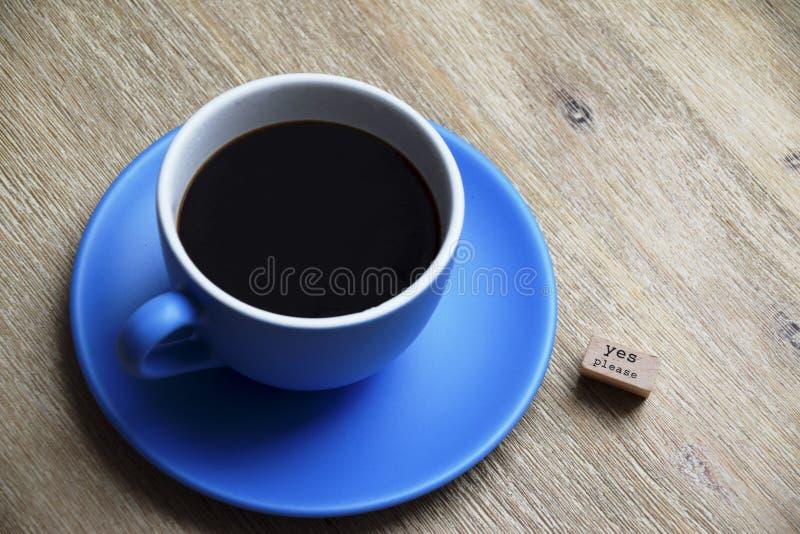 Ναι παρακαλώ στον καφέ σε ένα μπλε φλυτζάνι στοκ εικόνες