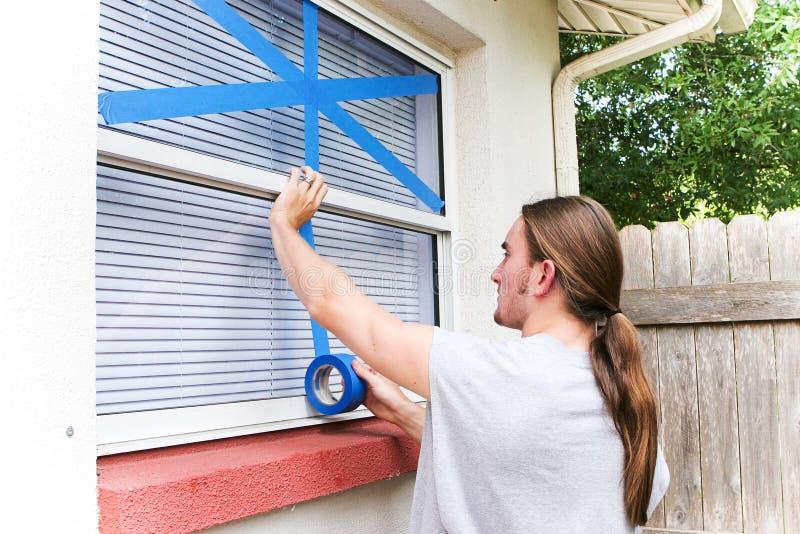Να δέσει τα παράθυρα για τον τυφώνα με ταινία στοκ εικόνα με δικαίωμα ελεύθερης χρήσης