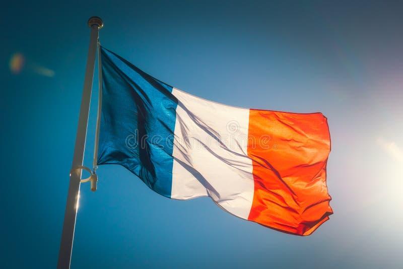 Να ανατρέξει σε μια όμορφη κυματίζοντας γαλλική σημαία ενάντια σε έναν μπλε ουρανό στοκ εικόνες με δικαίωμα ελεύθερης χρήσης