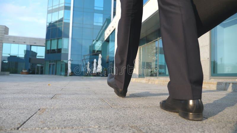 Να ανταλάξει επιχειρησιακών ατόμων στην εργασία Βέβαιος τύπος στο κοστούμι που είναι στο δρόμο του στο κτίριο γραφείων Νέος επιχε στοκ εικόνες