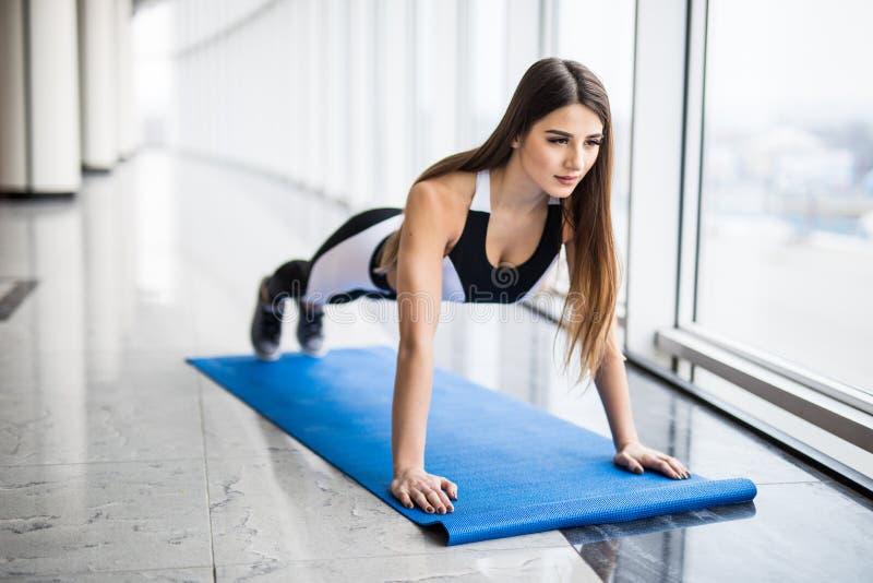 Να απασχοληθεί στους μυς πυρήνων της Πλήρες μήκος της νέας όμορφης γυναίκας sportswear που κάνει τη σανίδα στεμένος μπροστά από στοκ εικόνα
