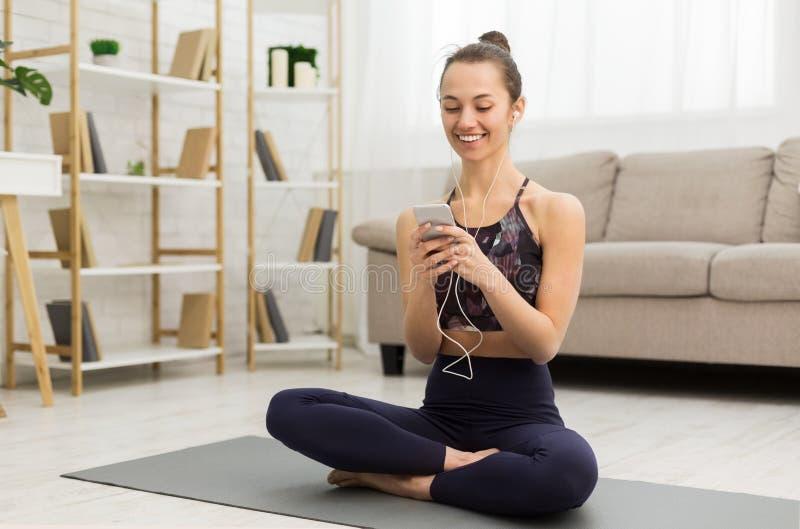 Να ασκήσει στο σπίτι Γυναίκα που έχει το υπόλοιπο, που χρησιμοποιεί το smartphone στοκ φωτογραφία με δικαίωμα ελεύθερης χρήσης