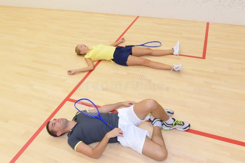 Να βρεθεί ζεύγους που εξαντλείται στο γήπεδο squash πατωμάτων στοκ φωτογραφία