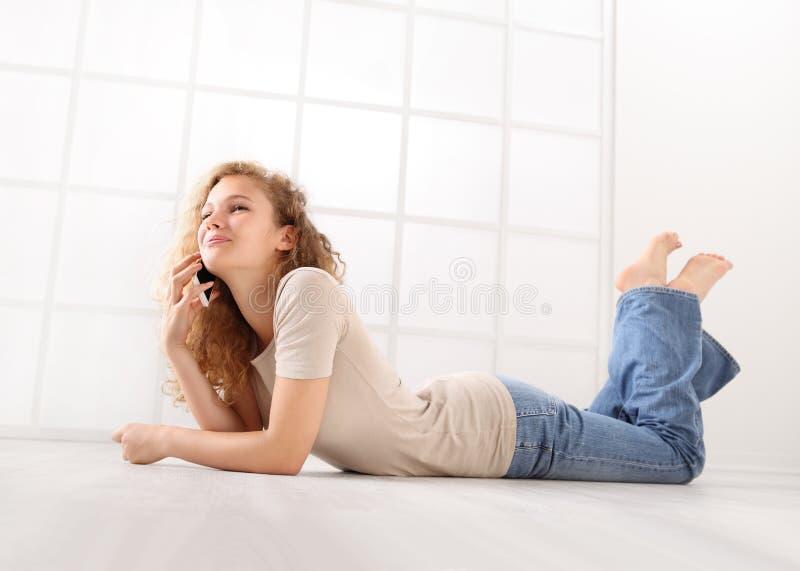 Να βρεθεί νέα γυναίκα στο πάτωμα που μιλά στο κινητό τηλέφωνο, με μακρυμάλλη στοκ φωτογραφία