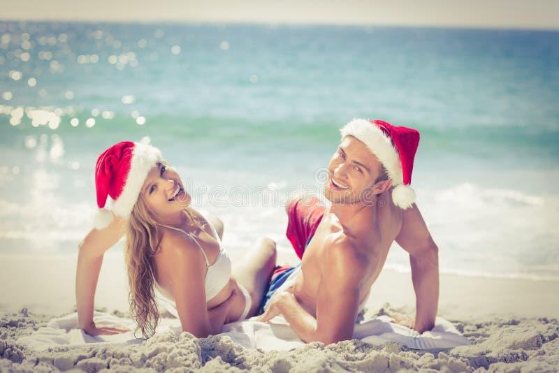Να βρεθεί χαριτωμένο ζεύγος που φορά τα καπέλα Χριστουγέννων στοκ φωτογραφία με δικαίωμα ελεύθερης χρήσης