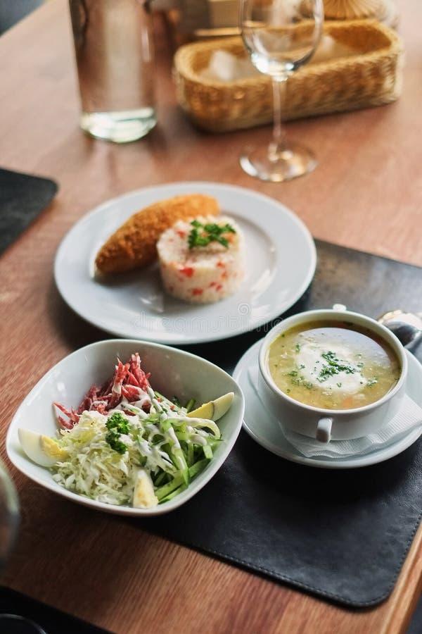 να δειπνήσει πίνακας: ένα πιάτο της σούπας, του risotto με cutlet και της φυτικής σαλάτας στοκ φωτογραφίες με δικαίωμα ελεύθερης χρήσης