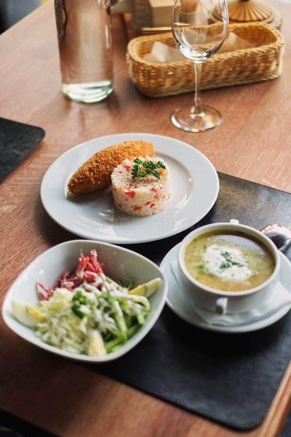 να δειπνήσει πίνακας: ένα πιάτο της σούπας, του risotto με cutlet και της φυτικής σαλάτας στοκ εικόνες με δικαίωμα ελεύθερης χρήσης