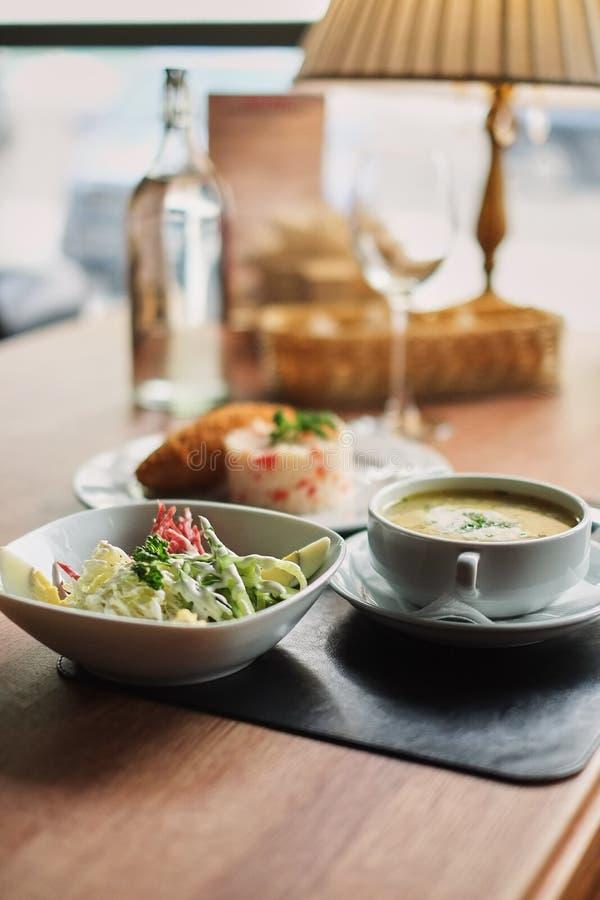 να δειπνήσει πίνακας: ένα πιάτο της σούπας, του risotto με cutlet και της φυτικής σαλάτας στοκ φωτογραφία με δικαίωμα ελεύθερης χρήσης