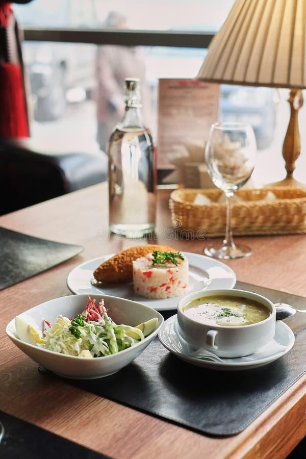 να δειπνήσει πίνακας: ένα πιάτο της σούπας, του risotto με cutlet και της φυτικής σαλάτας στοκ εικόνα
