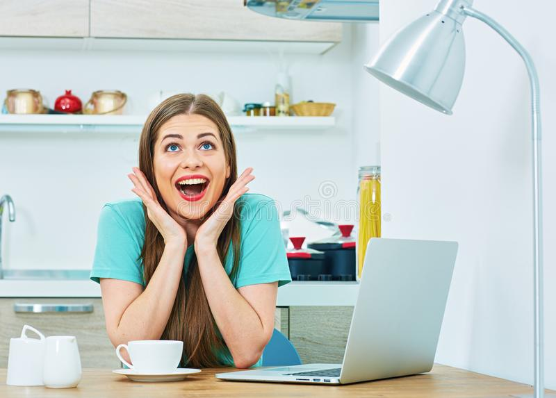 Να εκπλήξει τη γυναίκα με τη συνεδρίαση lap-top στην κουζίνα στοκ εικόνες