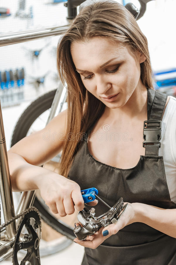 Να εμμείνει craftswoman επισκευάζοντας το πεντάλι στο γκαράζ στοκ φωτογραφία με δικαίωμα ελεύθερης χρήσης