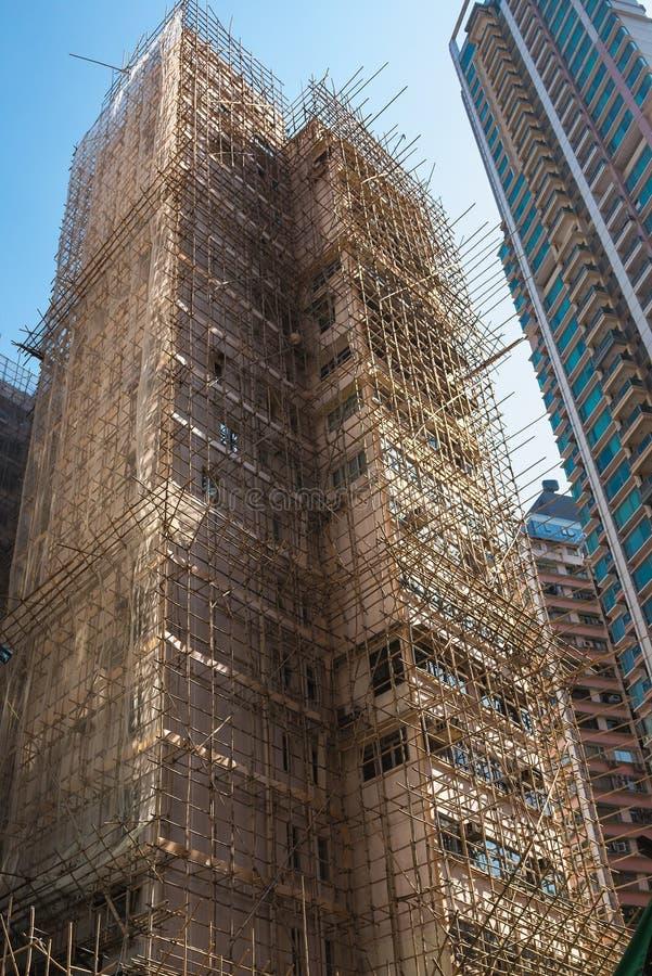 Να ενσωματώσει το Χονγκ Κονγκ είναι κάτω από την αναδημιουργία, που περιβάλλεται από τα υλικά σκαλωσιάς από το μπαμπού Αρχιτεκτον στοκ εικόνες