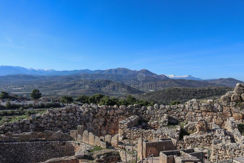 Να εξετάσει έξω πέρα από το οχυρό λόφων Mycenae Ελλάδα και το μουσείο και το χώρο στάθμευσης και πέρα από τα άλση καλλιεργήσιμου  στοκ φωτογραφία
