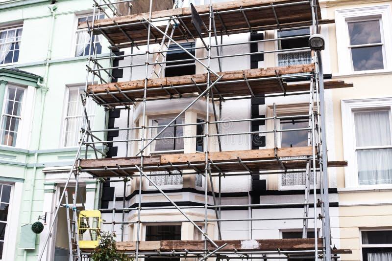 Να εξετάσει επάνω την οικοδόμηση των υλικών σκαλωσιάς ανακαίνισης Το κτήριο είναι κάτω από την οικοδόμηση, υλικά σκαλωσιάς μετάλλ στοκ εικόνες
