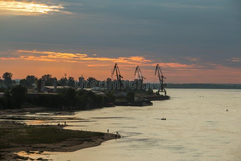 Να εξισώσει πέρα από το σιβηρικό ποταμό Σκιαγραφίες των γερανών στο λιμένα βιομηχανικό τοπίο στοκ εικόνα