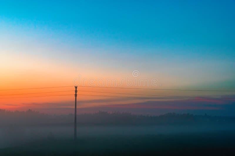 Να εξισώσει την παχιά ομίχλη πέρα από τον τομέα και το δασικό τοπίο του ουρανού βραδιού με το πορτοκάλι και του μπλε ουρανού και  στοκ εικόνες