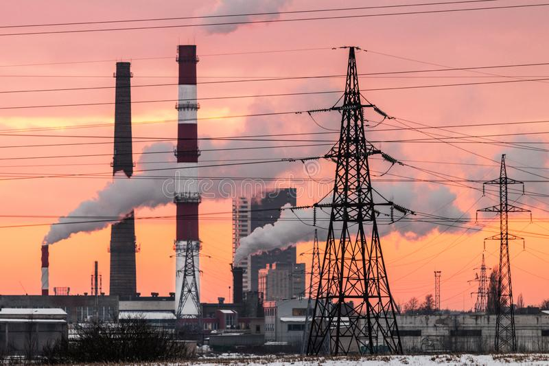 Να εξισώσει το βιομηχανικό τοπίο πόλεων με το κόκκινο υπόβαθρο ηλιοβασιλέματος στοκ εικόνα