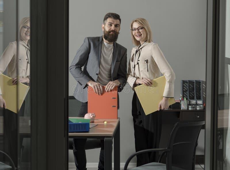 Να εργαστεί και να επικοινωνήσει από κοινού Ευτυχείς συνάδελφοι στο σύγχρονο γραφείο Συνεδρίαση του χαμόγελου επιχειρησιακών ζευγ στοκ εικόνα με δικαίωμα ελεύθερης χρήσης