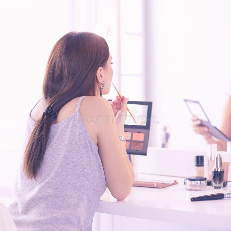 Να ισχύσει γυναικών Brunette αποζημιώνει μια ημερομηνία βραδιού μπροστά από έναν καθρέφτη στοκ εικόνες με δικαίωμα ελεύθερης χρήσης