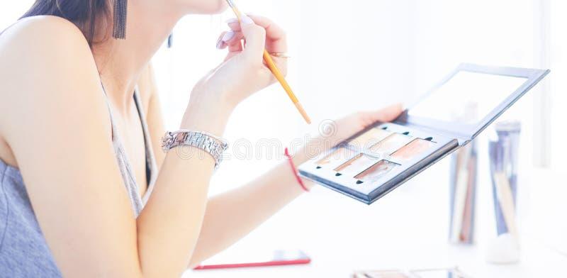 Να ισχύσει γυναικών Brunette αποζημιώνει μια ημερομηνία βραδιού μπροστά από έναν καθρέφτη στοκ εικόνα με δικαίωμα ελεύθερης χρήσης