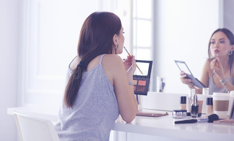 Να ισχύσει γυναικών Brunette αποζημιώνει μια ημερομηνία βραδιού μπροστά από έναν καθρέφτη στοκ φωτογραφία με δικαίωμα ελεύθερης χρήσης