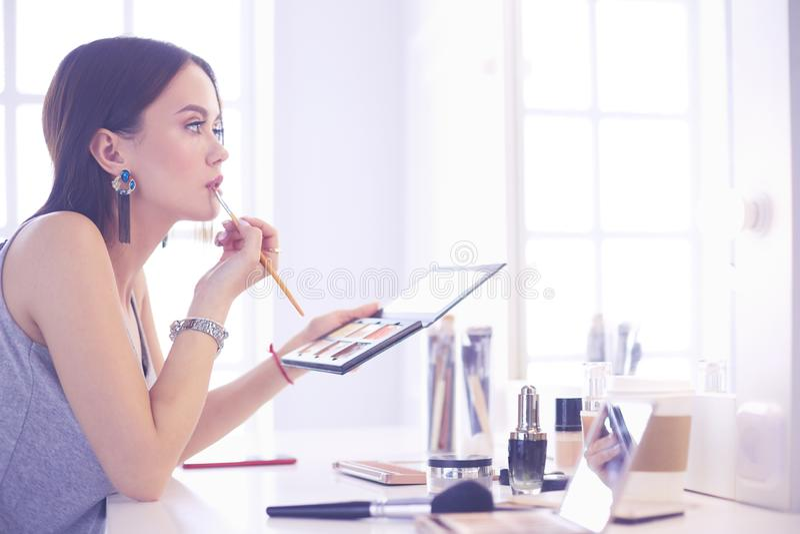 Να ισχύσει γυναικών Brunette αποζημιώνει μια ημερομηνία βραδιού μπροστά από έναν καθρέφτη στοκ εικόνες