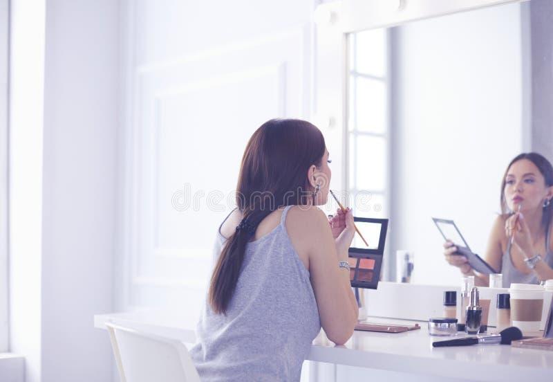 Να ισχύσει γυναικών Brunette αποζημιώνει μια ημερομηνία βραδιού μπροστά από έναν καθρέφτη στοκ εικόνα
