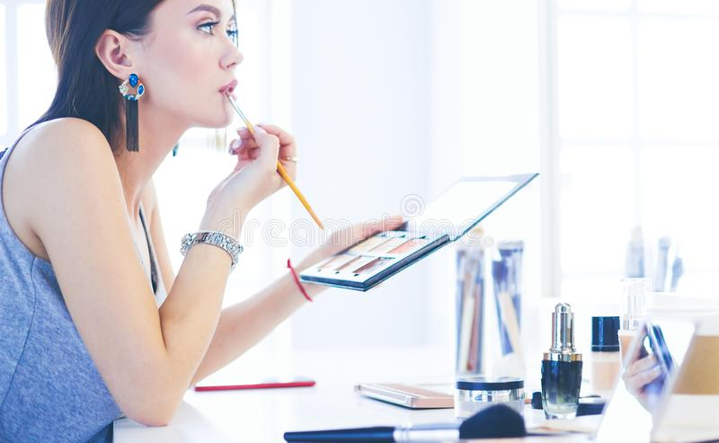 Να ισχύσει γυναικών Brunette αποζημιώνει μια ημερομηνία βραδιού μπροστά από έναν καθρέφτη στοκ φωτογραφίες με δικαίωμα ελεύθερης χρήσης