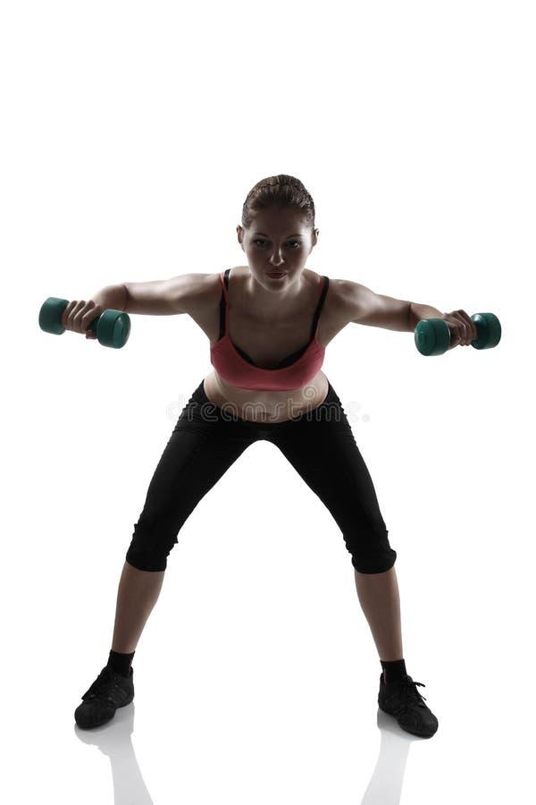Να κάνει νέο αθλητικό αθλητριών με τους αλτήρες, silhou στοκ φωτογραφίες