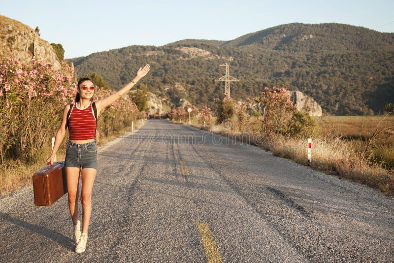 Να κάνει ωτοστόπ έννοια τουρισμού Hitchhiker ταξιδιού γυναίκα που περπατά στο δρόμο κατά τη διάρκεια του ταξιδιού με σκοπό τις δι στοκ εικόνα