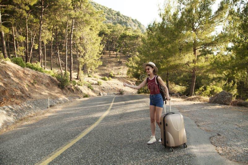 Να κάνει ωτοστόπ έννοια τουρισμού Hitchhiker ταξιδιού γυναίκα που περπατά στο δρόμο κατά τη διάρκεια του ταξιδιού με σκοπό τις δι στοκ εικόνες