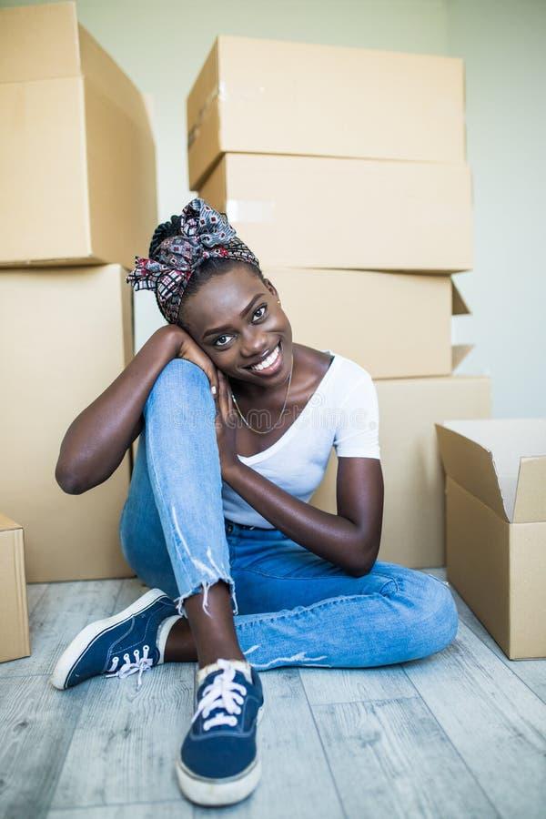 Να κινηθεί μέσα Γοητευτική νέα αφρικανική στάση κοριτσιών στα γόνατά της στο πάτωμα και χαμόγελο στη κάμερα παίρνοντας τα πιάτα α στοκ εικόνες