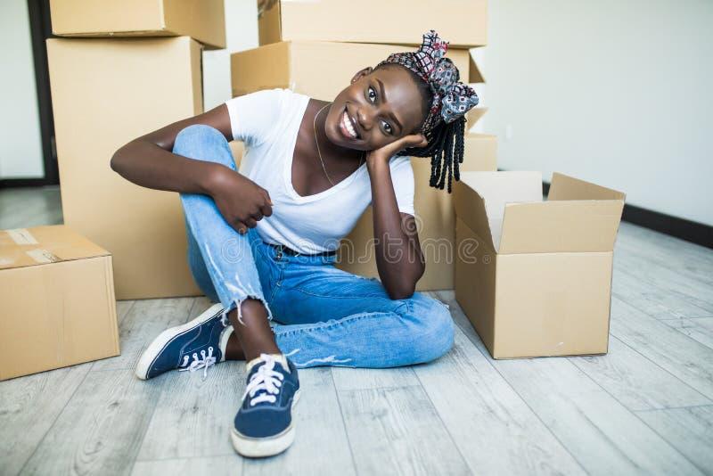 Να κινηθεί μέσα Γοητευτική νέα αφρικανική στάση κοριτσιών στα γόνατά της στο πάτωμα και χαμόγελο στη κάμερα παίρνοντας τα πιάτα α στοκ φωτογραφίες