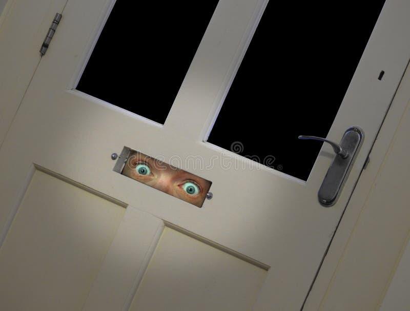να κοιτάξει επίμονα τα μάτια που κοιτάζουν αδιάκριτα μέσω του κιβωτίου επιστολών πορτών στοκ φωτογραφίες