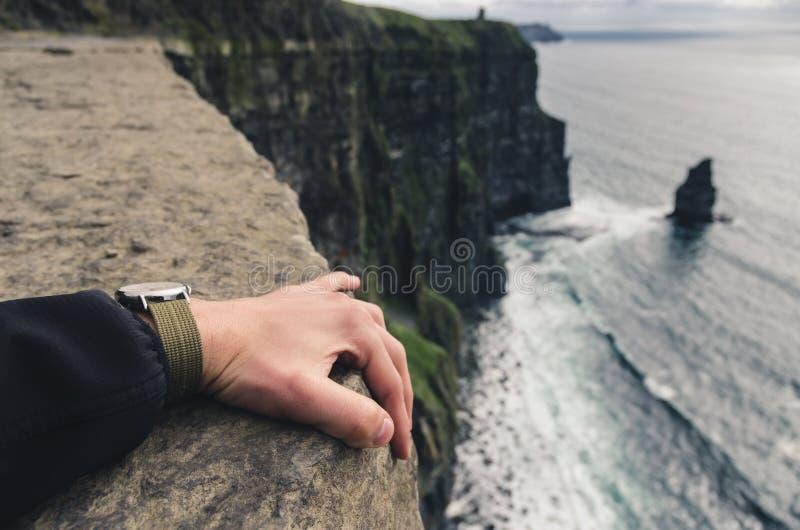 Να κρατήσει σφιχτά στην άκρη ενός απότομου βράχου στοκ φωτογραφία