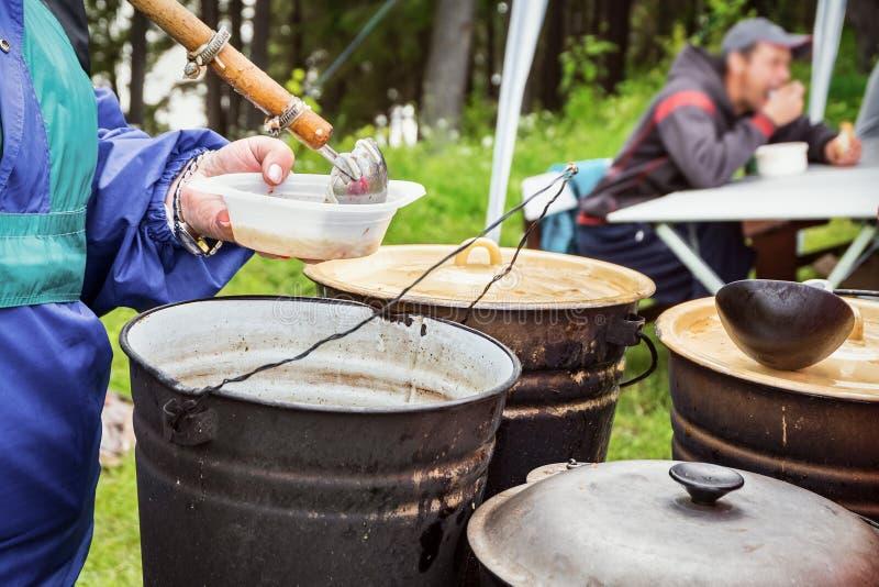 Να μαγειρεψει υπαίθρια Φιλανθρωπία Για να ταΐσει τον πεινασμένο άστεγο στοκ εικόνες