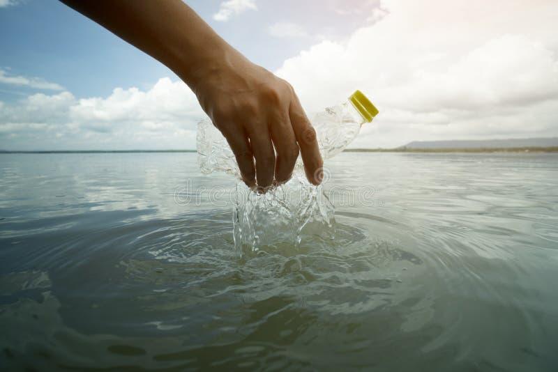 να μαζεψει με το χέρι επάνω το πλαστικό μπουκαλιών στη λίμνη, την ξηρασία και τα περιβαλλοντικά προβλήματα και την έννοια ρύπανση στοκ εικόνα
