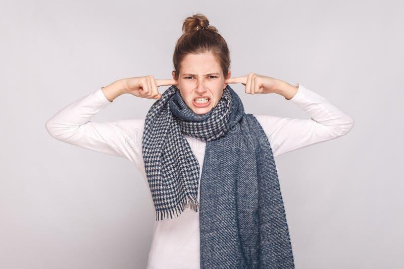 Να μην σας ακούσει! Άρρωστη νέα γυναίκα σχετικά με τα δάχτυλα τα αυτιά της στοκ φωτογραφίες
