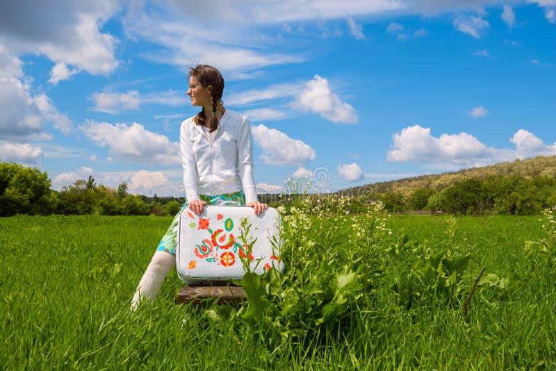 Να ονειρευτεί τις στάσεις κοριτσιών με μια χρωματισμένη βαλίτσα στοκ φωτογραφία με δικαίωμα ελεύθερης χρήσης
