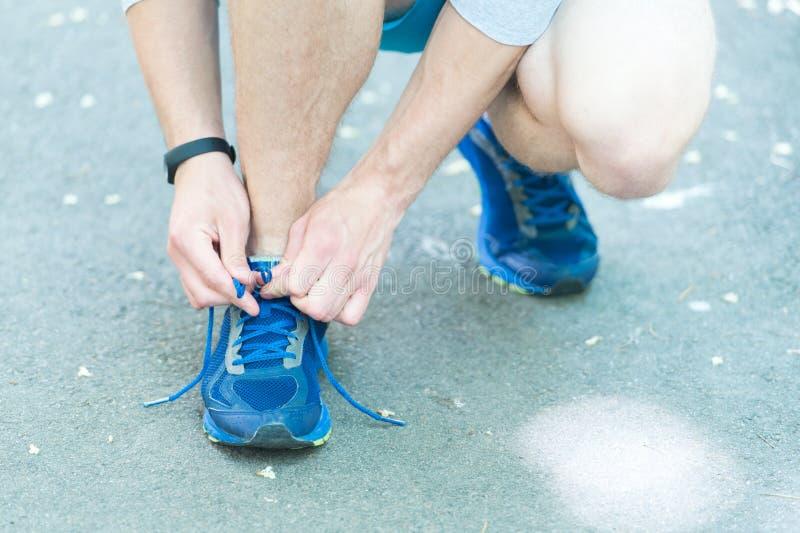 Να πάρει έτοιμος Δίνει το δένοντας πάνινο παπούτσι κορδονιών, οδικό υπόβαθρο Χέρια του αθλητικού τύπου με pedometer τη σύνδεση στοκ φωτογραφίες