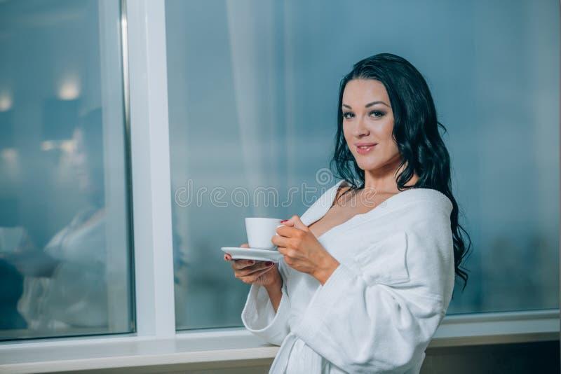 Να πάρει θερμός με το φρέσκο καφέ Όμορφη νέα γυναίκα στον άσπρο καφέ κατανάλωσης μπουρνουζιών και κοίταγμα μέσω ενός παραθύρου στοκ φωτογραφίες με δικαίωμα ελεύθερης χρήσης