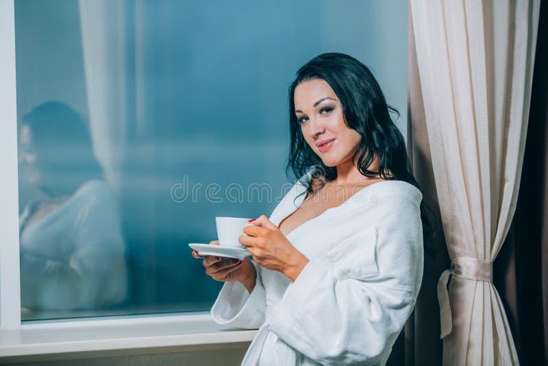 Να πάρει θερμός με το φρέσκο καφέ Όμορφη νέα γυναίκα στον άσπρο καφέ κατανάλωσης μπουρνουζιών και κοίταγμα μέσω ενός παραθύρου στοκ εικόνες