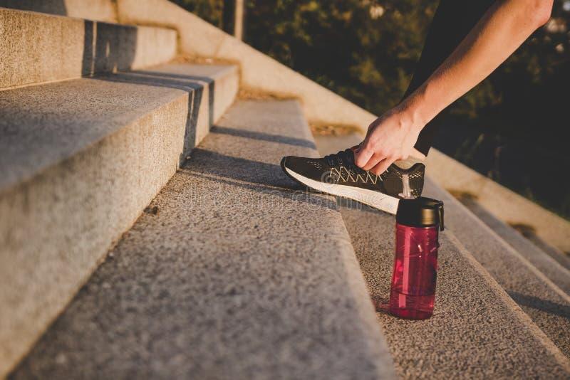 Να προετοιμαστεί για το τρέξιμο Νέα γυναίκα που δένει τα τρέχοντας παπούτσια της στο πάρκο στοκ φωτογραφίες
