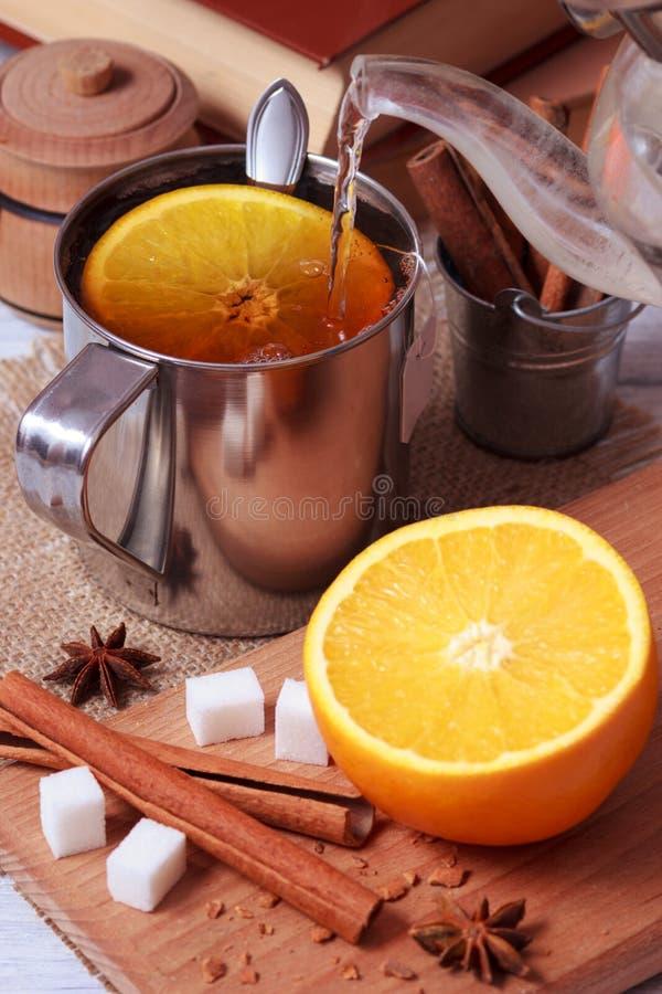 Να προετοιμαστεί του μαύρου τσαγιού στο μεταλλικό φλυτζάνι με τα πορτοκαλιά φρούτα στοκ φωτογραφία με δικαίωμα ελεύθερης χρήσης