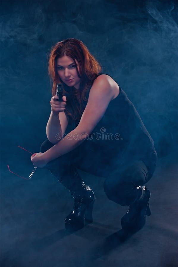 να στοχεύσει το σκύψιμο κάτω από τη γυναίκα πυροβόλων όπλων στοκ φωτογραφίες με δικαίωμα ελεύθερης χρήσης
