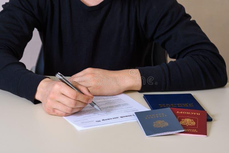 Να συμπληρώσει μια σύμβαση απασχόλησης και ένα αρχείο απασχόλησης, το διαβατήριο και το δίπλωμα στον πίνακα στοκ εικόνα