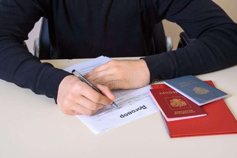 Να συμπληρώσει μια σύμβαση απασχόλησης και ένα αρχείο απασχόλησης, το διαβατήριο και το δίπλωμα στον πίνακα στοκ φωτογραφίες