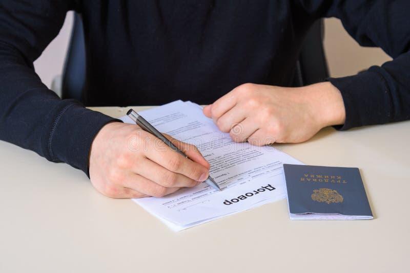Να συμπληρώσει μια σύμβαση απασχόλησης και ένα βιβλίο αρχείων απασχόλησης στοκ φωτογραφίες