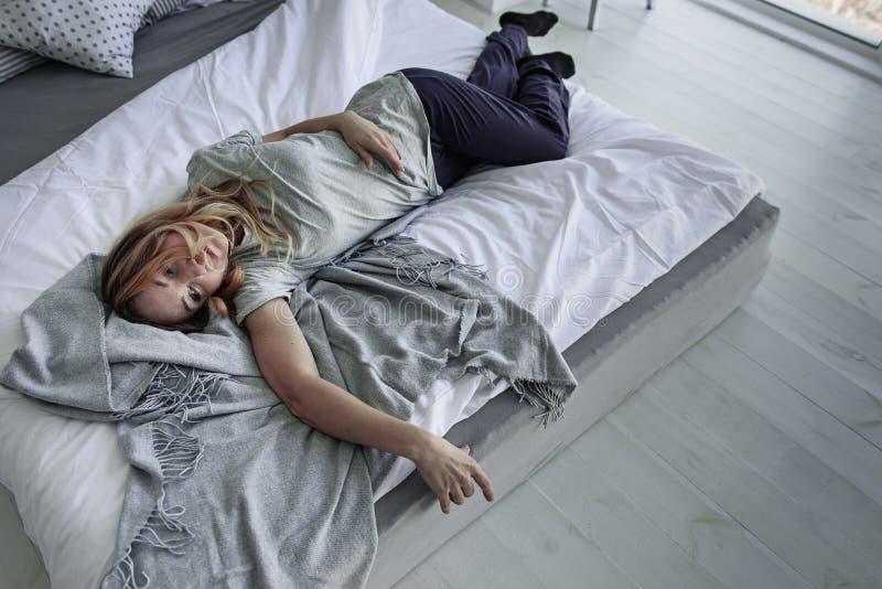 Να υποστεί το θηλυκό πρόσωπο που βρίσκεται στο κρεβάτι στοκ φωτογραφίες με δικαίωμα ελεύθερης χρήσης